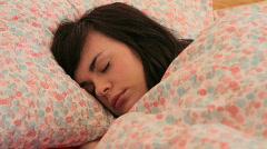 Female sleeping in bed under duvet Stock Footage