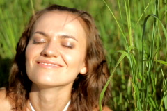 Smiling Woman in grassfields flirting with camera Stock Footage