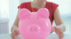Female lifting piggy bank to check her savings - stock footage
