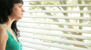 Female looking out of window Stock Footage