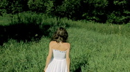 Woman in white dress walking on a green meadow, slow motion Stock Footage