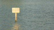 Stock Video Footage of No Swimming No Wading Warning Sign in Water LS