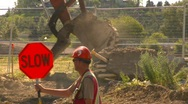 Stock Video Footage of construction, backhoe tractor loading dirt, safety man and traffic
