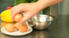 The cook breaks eggs in a bowl - stock footage