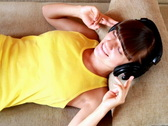 Stock Video Footage of Happy woman with headphones lying down on sofa