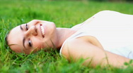 Stock Video Footage of Young happy woman lying on the grass, dolly shot