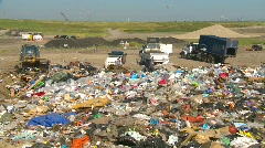The environment, garbage dump, #19 and trucks, garbage foreground, wide shot Stock Footage