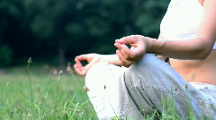 Woman sitting on the grass in park and meditating, dolly shot Stock Footage