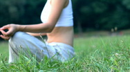Stock Video Footage of Woman sitting on the grass in park and meditating, dolly shot