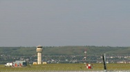 Stock Video Footage of aircraft, Bombardier RJ jet landing through frame with ATC tower in background