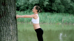 Woman exercises by the tree in the park Stock Footage
