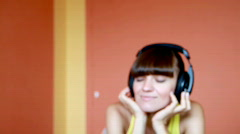 Attractive woman with headphones listening to music, dolly shot Stock Footage