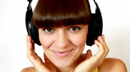 Attractive woman with headphones listening to music, isolated over a white backg Stock Footage