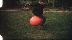 Boy hopping on ball (vintage 8 mm amateur film) Stock Footage
