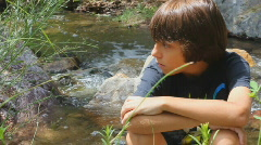 Somber or sad pre-teen boy sitting at stream  - 1 Stock Footage