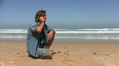 Young guy making a phonecall at the beach Stock Footage