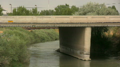 A River Runs Under A Bridge As Cars Drive Over It Stock Footage