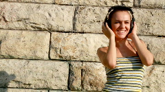 Attractive woman with headphones outdoor, tracking shot Stock Footage