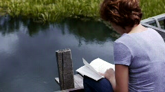 Stock Video Footage girl reading by the pond - stock footage