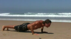 Young man doing sports exercises on the beach  Stock Footage