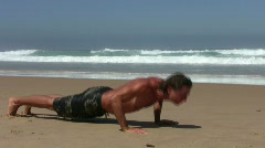 Young guy doing fitness excersises on the beach Stock Footage