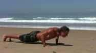 Stock Video Footage of Young guy doing fitness excersises on the beach