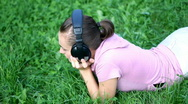 Stock Video Footage of Attractive woman with headphones lying on the grass