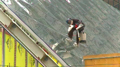 Construction, high angle worker above street, LRT and people Stock Footage