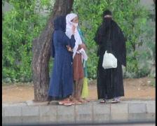 Women In Burqahs Standing in Rain Stock Footage