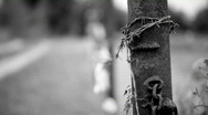 Stock Video Footage of Metal fence with barbed wire, wound on a rusty iron pipe