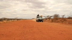 Vehicle Drives by on Dusty Road in Kenya (HD) co Stock Footage