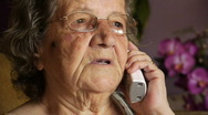 Old retired woman talking on telephone  Stock Footage