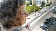 Stock Video Footage of Old retired woman watching traffic from balcony