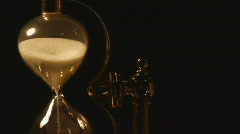 Sand flows in glass hourglass - stock footage