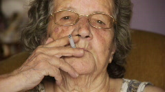 Old retired woman smoking cigarette Stock Footage