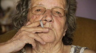 Stock Video Footage of Old retired woman smoking cigarette