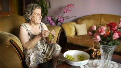 Old retired woman eating grapes in home  Stock Footage