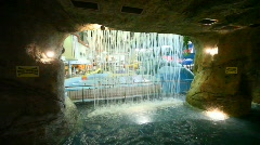 Through a waterfall of stone cave seen people bathing in pool in waterpark Stock Footage