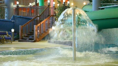 Woman runs under fountain in a pool in indoor water park Stock Footage