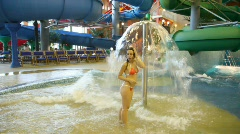 Woman stands under a fountain in a pool in indoor water park Stock Footage