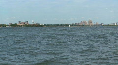 Ferry passing by ellis island Stock Footage