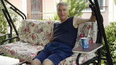 Old retired man on porch swing  Stock Footage