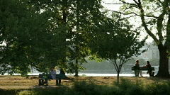 people seated along the charles at sunset - stock footage