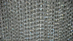 Curtain of beads above a mirror set in motion by the airflow coming from outisde Stock Footage