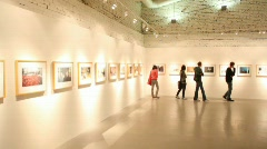 Visitors walks and looks at pictures in exhibition hall Stock Footage
