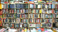 Books on bookshelves and shopboard in bookshop Stock Footage