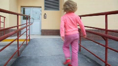 Girl comes to door of apartment block and using entrance door intercom Stock Footage