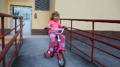 Little girl pedaling on bicycle near apartment block Stock Footage
