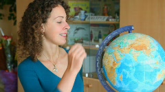 Beautiful schoolteacher selecting continents and countries on globe Stock Footage