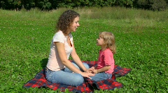 Woman and daughter sits on summer field in park Stock Footage
